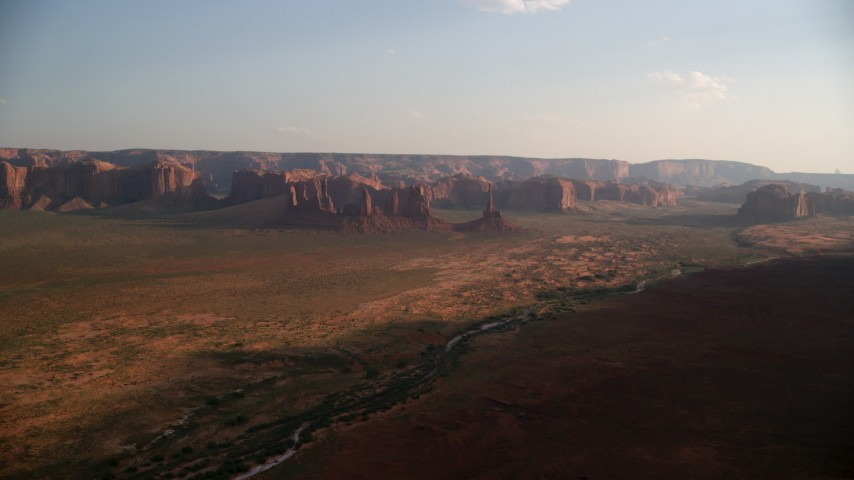 Approaching buttes, mesas across desert, Monument Valley, Utah, Arizona, twilight Aerial Stock Footage | AX133_034