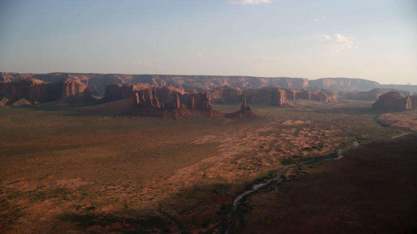 Approaching buttes, mesas, across desert, Monument Valley, Utah, Arizona, twilight Aerial Stock Footage | AX133_035