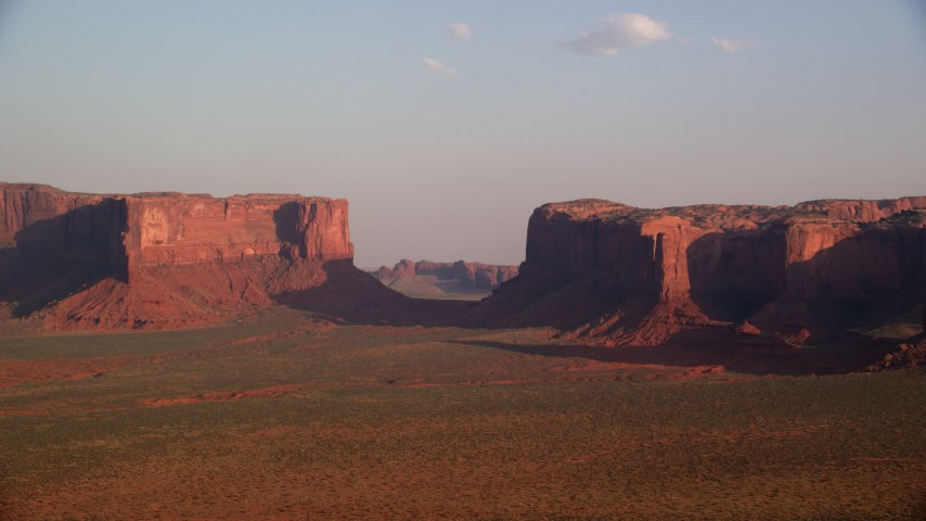 Flying by mesas, across desert valley, Monument Valley, Utah, Arizona, twilight Aerial Stock Footage | AX133_036