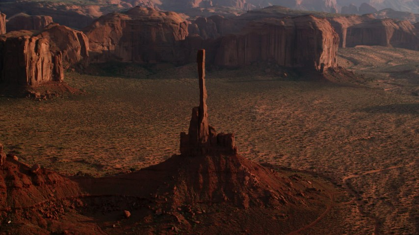 Flying by Totem Pole Butte, Monument Valley, Utah, Arizona, twilight Aerial Stock Footage AX133_039
