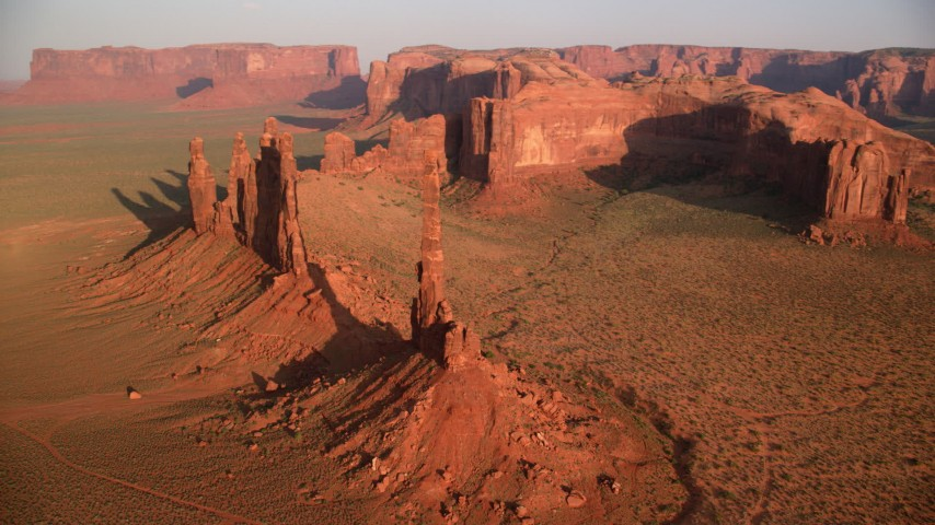 Orbiting buttes in desert valley, Monument Valley, Utah, Arizona, twilight Aerial Stock Footage | AX133_041