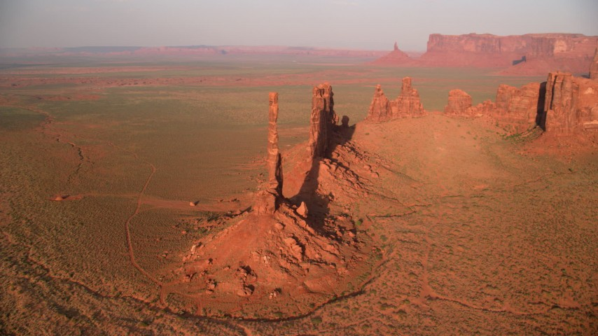 Orbiting buttes in desert valley, Monument Valley, Utah, Arizona, twilight Aerial Stock Footage AX133_042