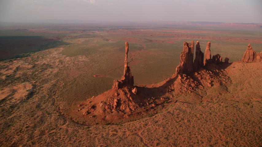 Orbiting buttes in desert valley, Monument Valley, Utah, Arizona, twilight Aerial Stock Footage | AX133_043