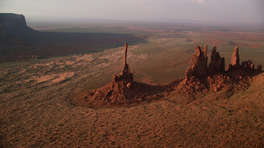 Orbiting buttes in desert valley, Monument Valley, Utah, Arizona, twilight Aerial Stock Footage AX133_044