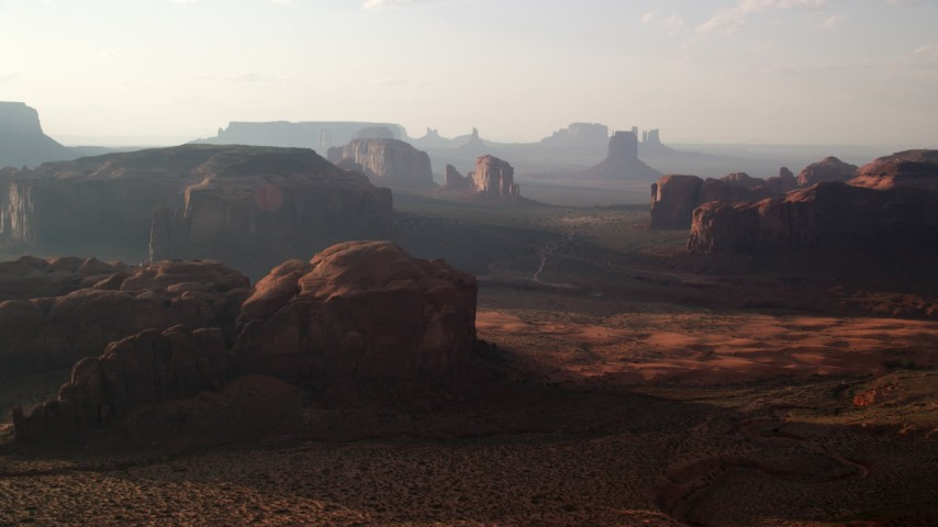 Flying by buttes and mesas, Monument Valley, Utah, Arizona, twilight Aerial Stock Footage | AX133_046
