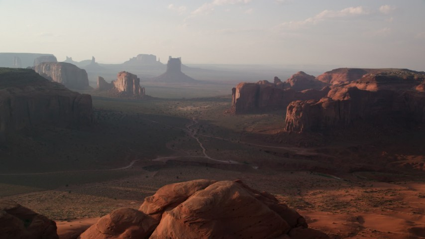 Flying by buttes, mesas, Monument Valley, Utah, Arizona, twilight Aerial Stock Footage | AX133_048