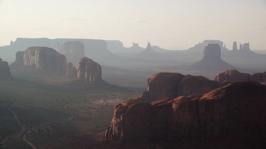Flying by mesas and buttes, Monument Valley, Utah, Arizona, twilight Aerial Stock Footage | AX133_050