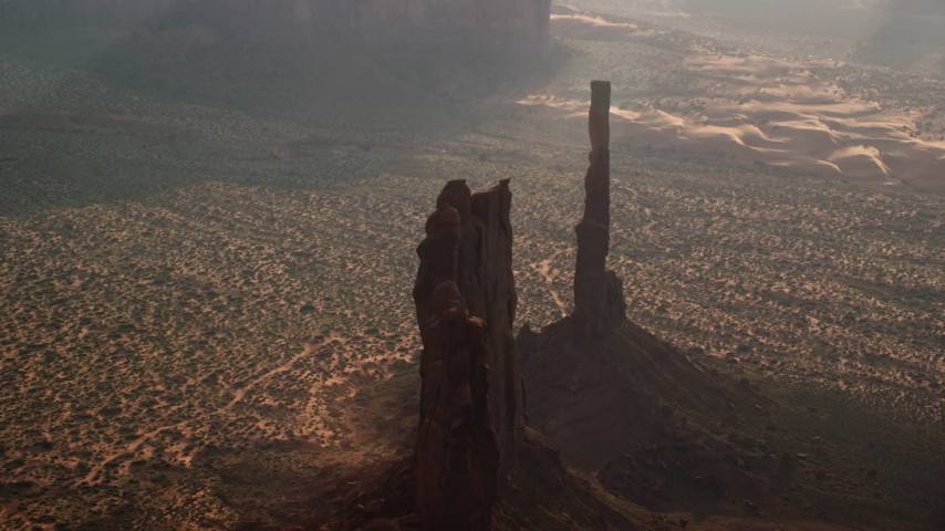 Flying away from Totem Pole Butte, Monument Valley, Utah, Arizona, twilight Aerial Stock Footage | AX133_051
