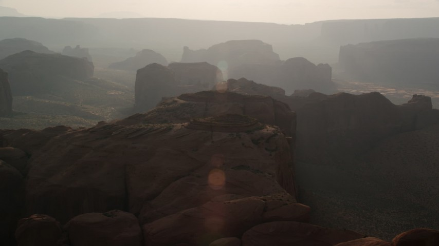 Flying by mesas and buttes, Monument Valley, Utah, Arizona, sunset Aerial Stock Footage | AX133_052