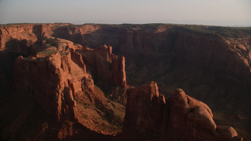 Flying by Hunt's Mesa, rock formations, Monument Valley, Utah, Arizona, sunset Aerial Stock Footage | AX133_054