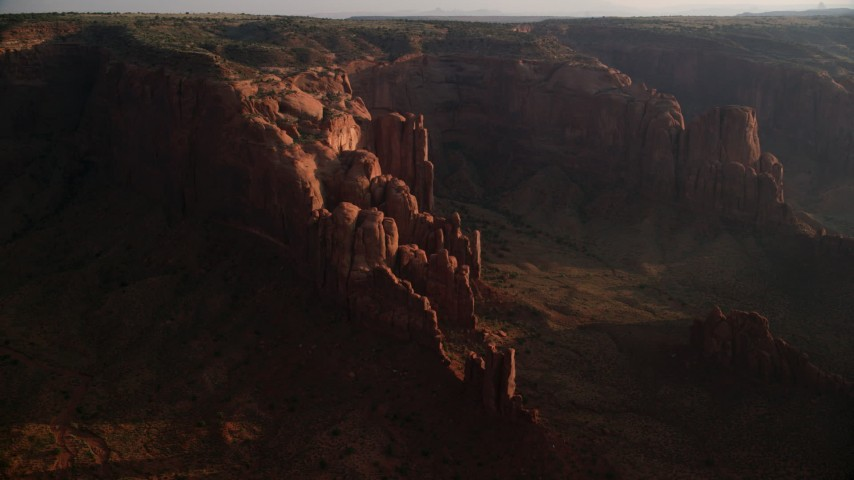 Flying by rock formations, Hunt's Mesa, Monument Valley, Utah, Arizona, sunset Aerial Stock Footage | AX133_055