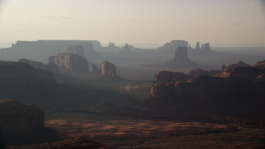 Flying by mesas and buttes, Monument Valley, Utah, Arizona, sunset Aerial Stock Footage   AX133_058