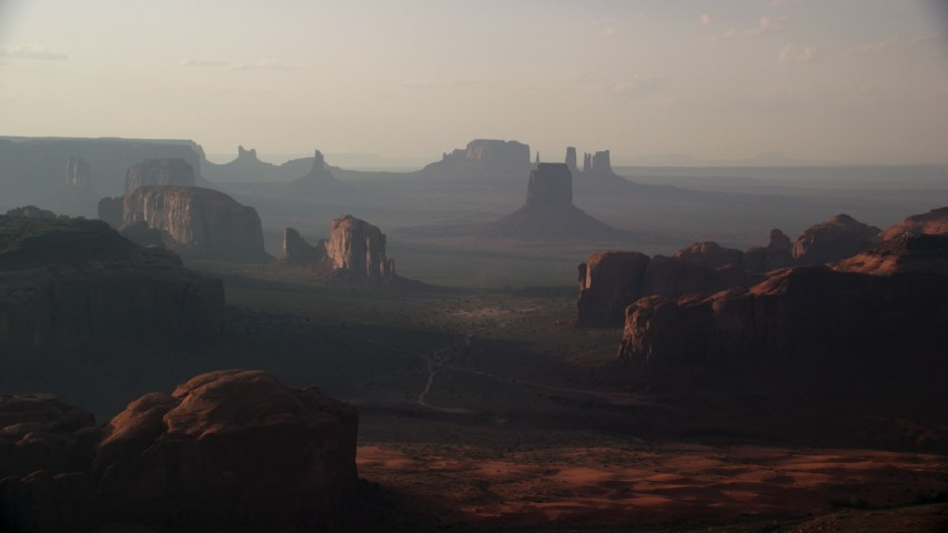 Flying by mesas and buttes, Monument Valley, Utah, Arizona, sunset Aerial Stock Footage | AX133_059