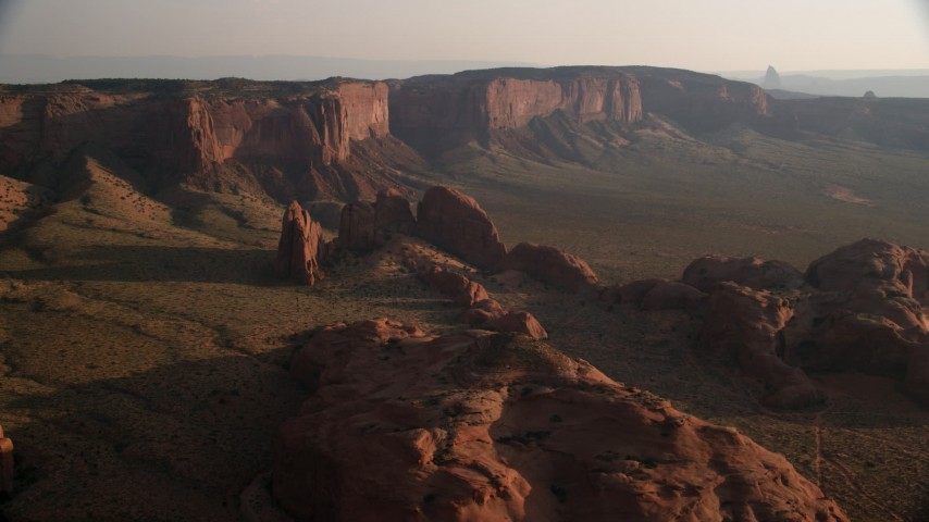 Flying by rock formations and Hunt's Mesa, Monument Valley, Utah, Arizona, sunset Aerial Stock Footage | AX133_061