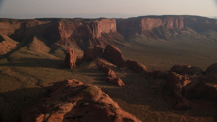 Flying by rock formations and Hunt's Mesa, Monument Valley, Utah, Arizona, sunset Aerial Stock Footage | AX133_062