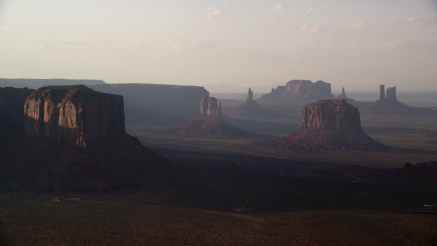 Flying by buttes in a desert valley, Monument Valley, Utah, Arizona, twilight Aerial Stock Footage | AX133_065