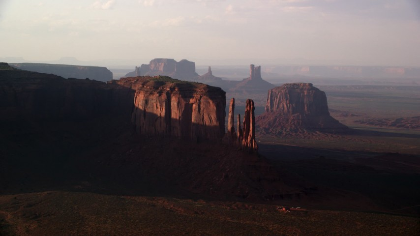 Flying by buttes in a desert valley, Monument Valley, Utah, Arizona, twilight Aerial Stock Footage | AX133_068