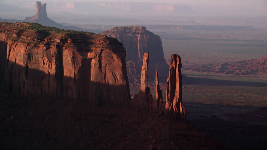 Flying by Mitchell Mesa, Three Sisters, Monument Valley, Utah, Arizona, twilight Aerial Stock Footage | AX133_069