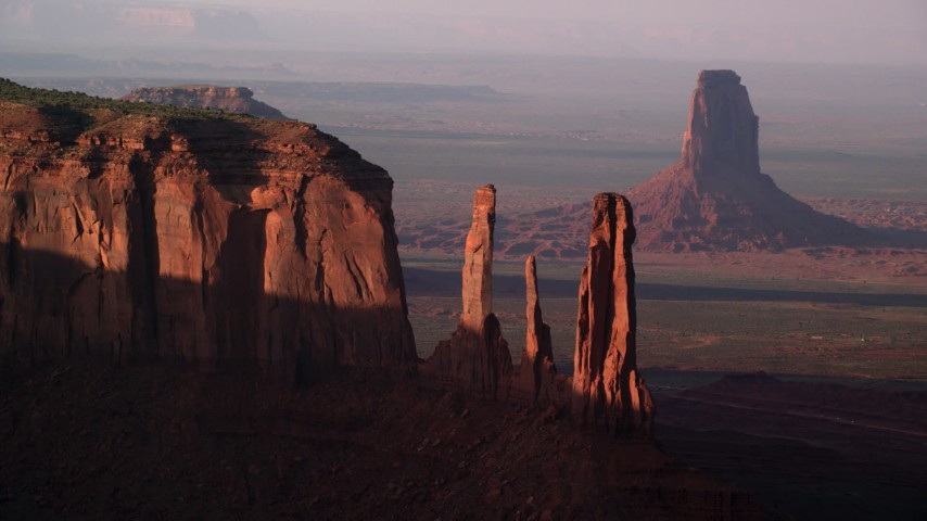 Flying by Three Sisters, Mitchell Mesa, Monument Valley, Utah, Arizona, twilight Aerial Stock Footage   AX133_070
