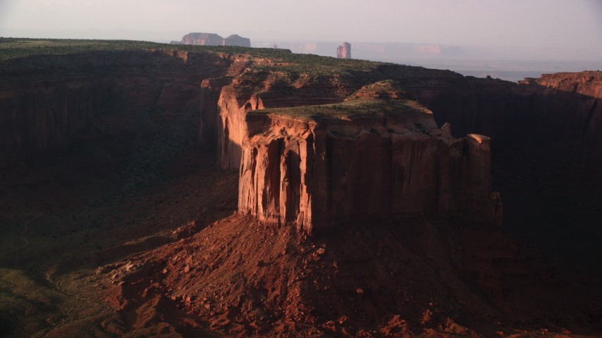 Flying by Mitchell Mesa, Monument Valley, Utah, Arizona, twilight Aerial Stock Footage | AX133_071