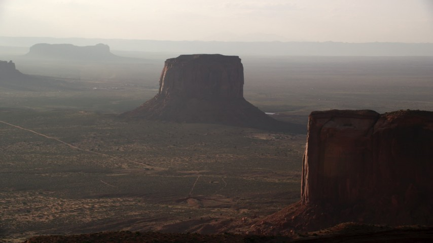 Approaching Mitchell Butte, Monument Valley, Utah, Arizona, twilight Aerial Stock Footage | AX133_074