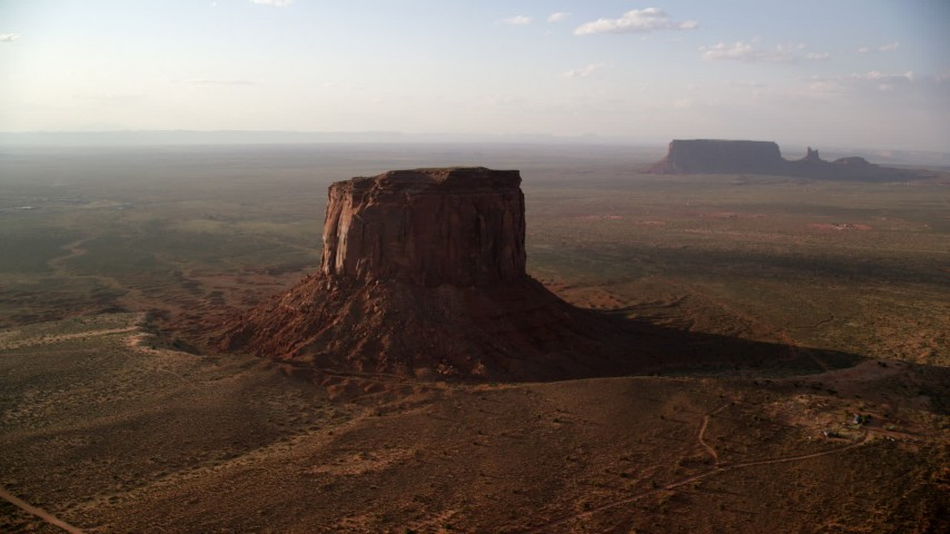 Flying by Mitchell Butte, Monument Valley, Utah, Arizona, twilight Aerial Stock Footage | AX133_078