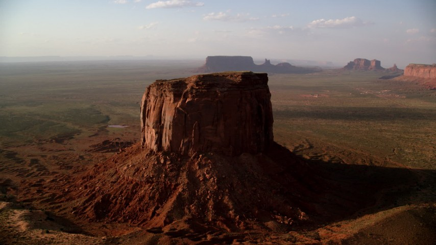 Flying by Mitchell Butte, Monument Valley, Utah, Arizona, twilight Aerial Stock Footage | AX133_079