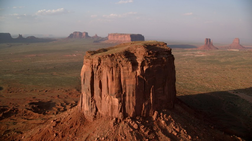 Flying by Mitchell Butte, Monument Valley, Utah, Arizona, sunset Aerial Stock Footage | AX133_080