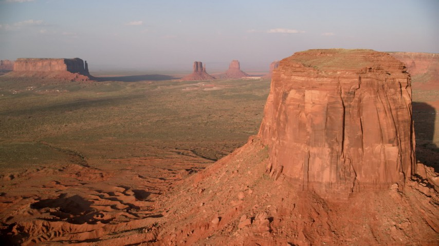 Flying by buttes, desert valley, Monument Valley, Utah, Arizona, sunset Aerial Stock Footage | AX133_081