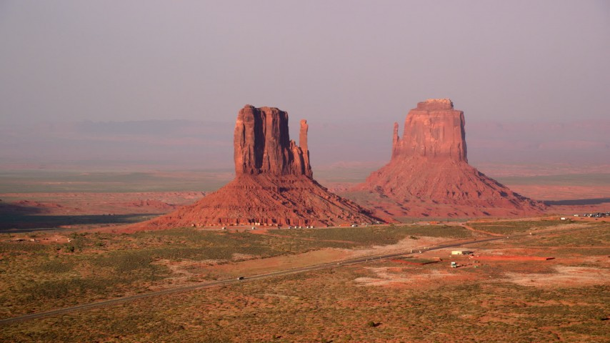 Flying by West and East Mitten Buttes, Monument Valley, Utah, Arizona, twilight Aerial Stock Footage | AX133_082