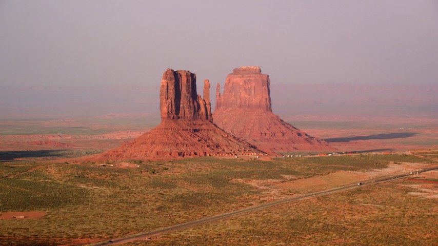 Flying by West and East Mitten Buttes, Monument Valley, Utah, Arizona, twilight Aerial Stock Footage | AX133_083