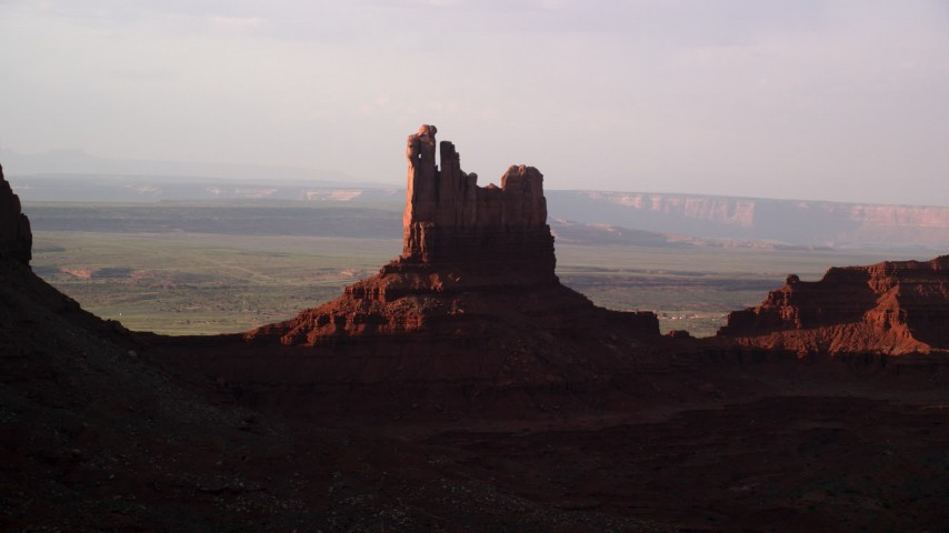 Flying by Setting Hen Butte, Monument Valley, Utah, Arizona, twilight Aerial Stock Footage | AX133_090