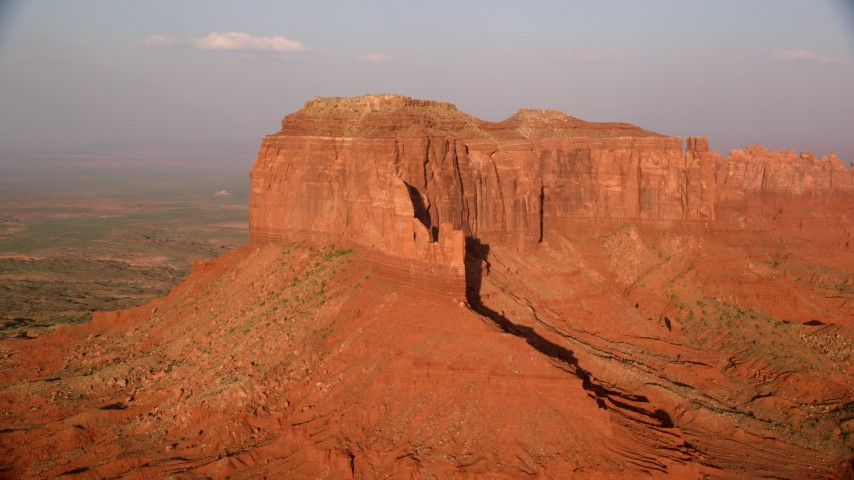 Flying by Brighams Tomb Butte, Monument Valley, Utah, Arizona, sunset Aerial Stock Footage | AX133_093