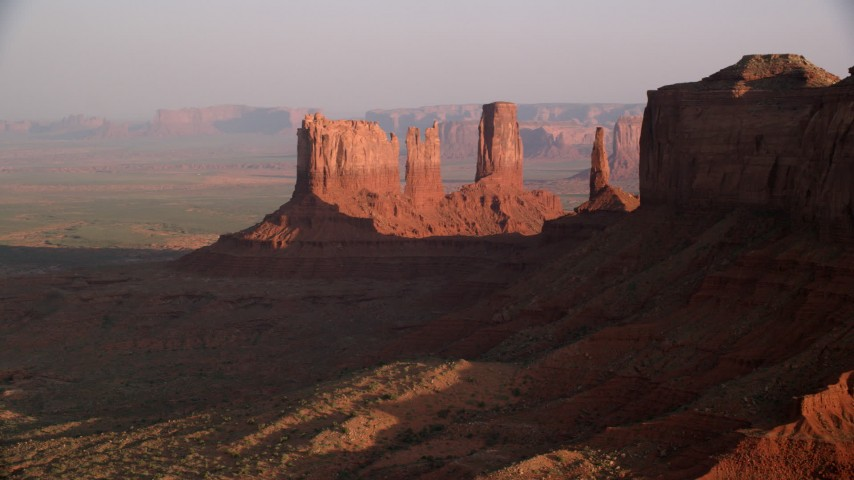 Flying by buttes, desert valley, Monument Valley, Utah, Arizona, twilight Aerial Stock Footage | AX133_095