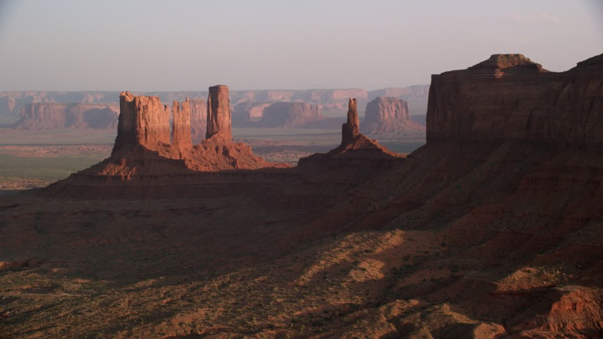 Flying by buttes, desert valley, Monument Valley, Utah, Arizona, twilight Aerial Stock Footage | AX133_096
