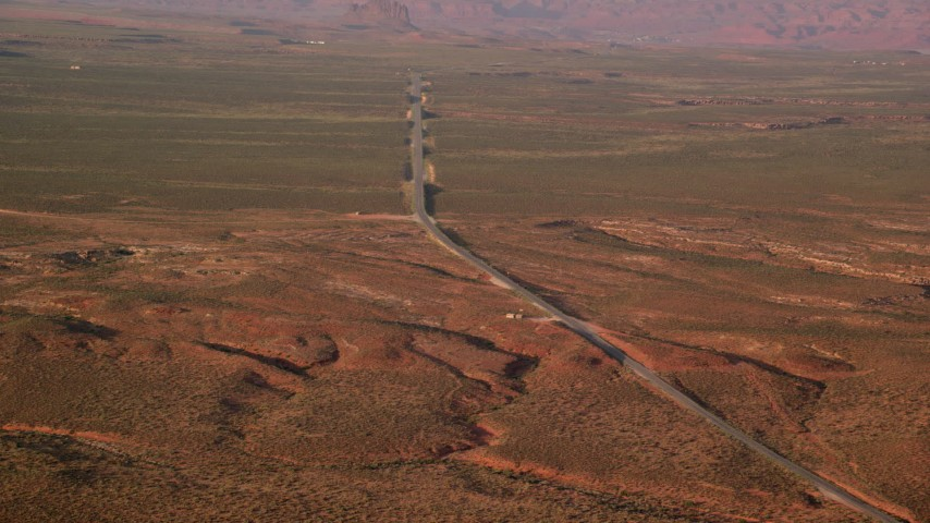 Flying by Highway 163, Monument Valley, Utah, Arizona, twilight Aerial Stock Footage | AX133_097