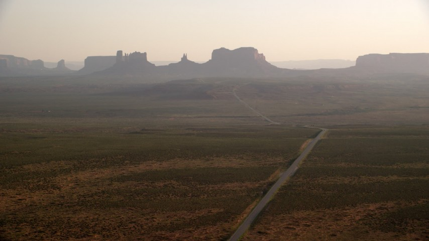 Flying by Highway 163, buttes, mesas, Monument Valley, Utah, Arizona, twilight Aerial Stock Footage | AX133_100