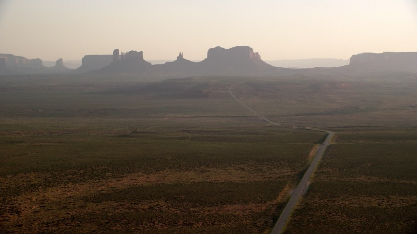 Fly by highway, leading to buttes, mesas, Monument Valley, Utah, Arizona, twilight Aerial Stock Footage | AX133_101