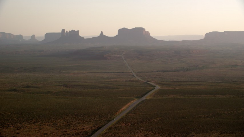 6K stock footage aerial video of wide view of highway leading to buttes and mesas in Monument Valley, Utah, Arizona, twilight Aerial Stock Footage | AX133_102