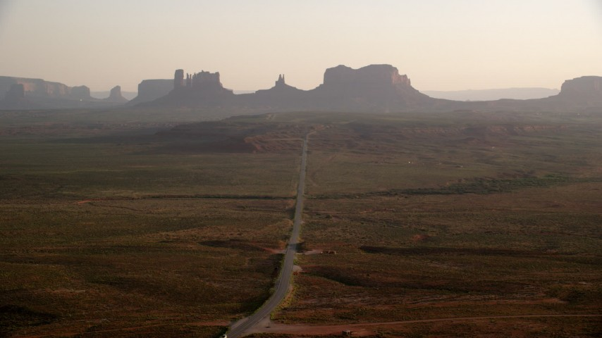 6K stock footage aerial video fly over highway, approach buttes and mesas, Monument Valley, Utah, Arizona, twilight Aerial Stock Footage | AX133_104