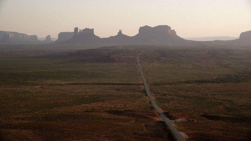 Flying by highway leading to buttes, Monument Valley, Utah, Arizona, twilight Aerial Stock Footage | AX133_105