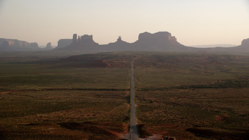 Fly over highway toward buttes, Monument Valley, Utah, Arizona, twilight Aerial Stock Footage | AX133_106