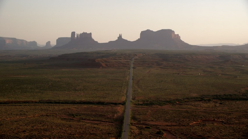 Fly over highway toward buttes, Monument Valley, Utah, Arizona, twilight Aerial Stock Footage | AX133_107