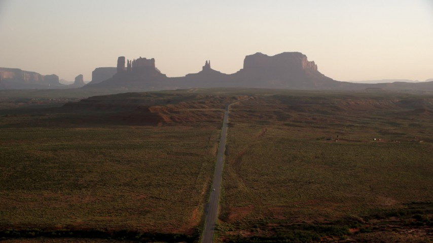 Fly over highway toward buttes, Monument Valley, Utah, Arizona, twilight Aerial Stock Footage | AX133_108