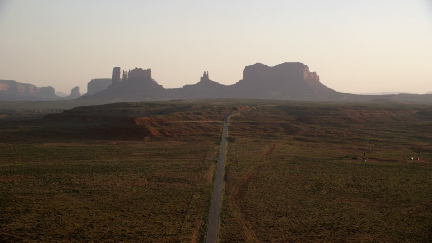 Fly over highway, approaching buttes, Monument Valley, Utah, Arizona, twilight Aerial Stock Footage | AX133_109