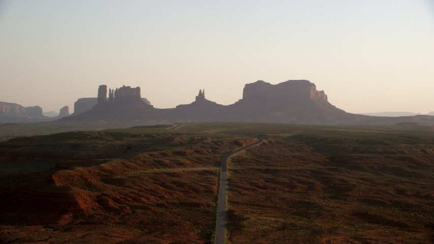 Fly over highway, approaching buttes, Monument Valley, Utah, Arizona, twilight Aerial Stock Footage | AX133_111
