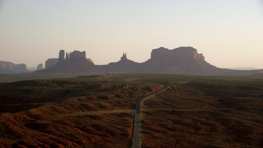 6K stock footage aerial video of flying toward buttes, following highway in Monument Valley, Utah, Arizona, twilight Aerial Stock Footage | AX133_112