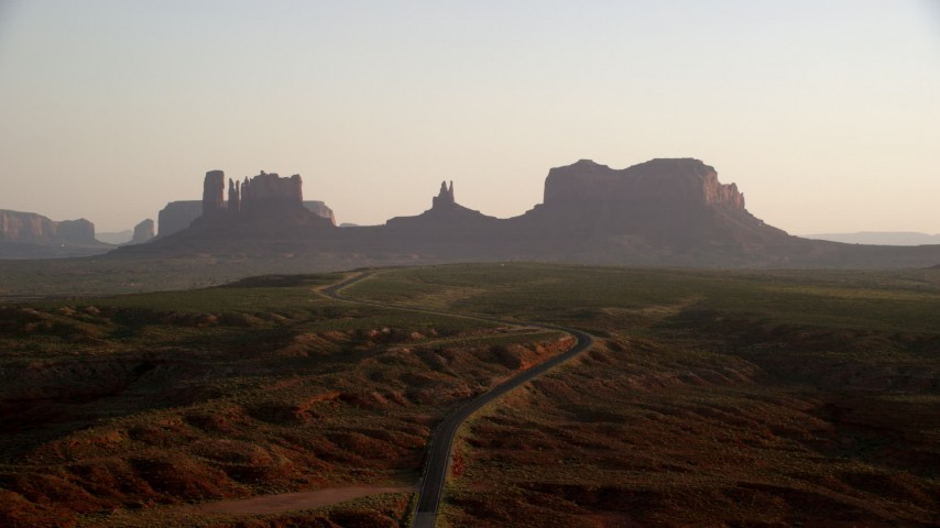 Fly by highway leading to buttes, Monument Valley, Utah, Arizona, twilight Aerial Stock Footage | AX133_113