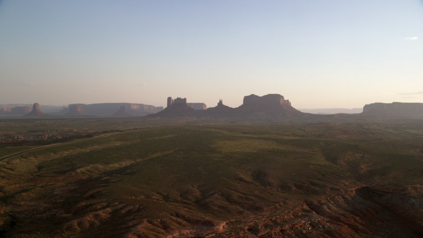 6K stock footage aerial video of approaching buttes near highway, Monument Valley, Utah, Arizona, twilight Aerial Stock Footage | AX133_115