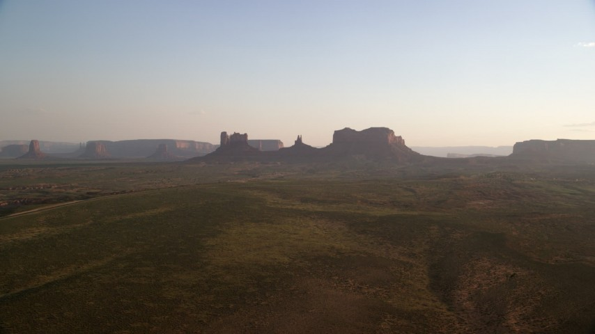 Approaching buttes, mesa, Monument Valley, Utah, Arizona, twilight Aerial Stock Footage | AX133_116